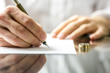 Uncontested divorce attorney Orlando – 2 hands on table signing a document